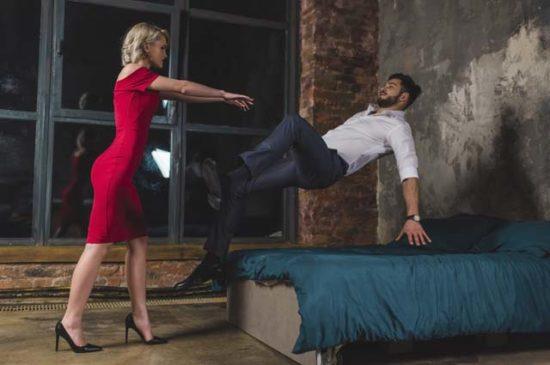 Женщина бросает мужчину на кровать