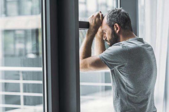 Мужчина у окна расстроен