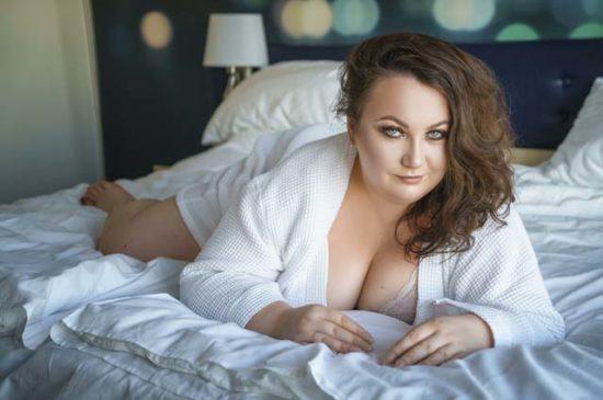Пышная девушка лежит на кровати