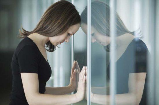 Девушка расстроена, облокотилась на стеклянную стену