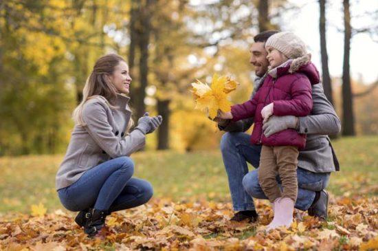 Молодая пара с дочкой в парке осенью