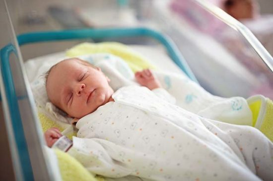 Новорожденный ребенок в палате роддома