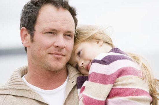 Отец держит дочь на руках