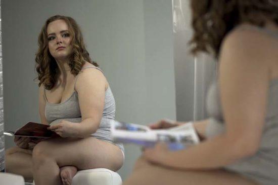 Полная девушка критически смотрит в зеркало
