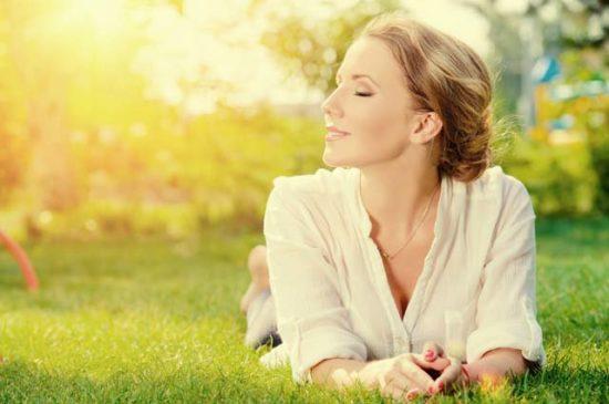 Счастливая женщина лежит на траве
