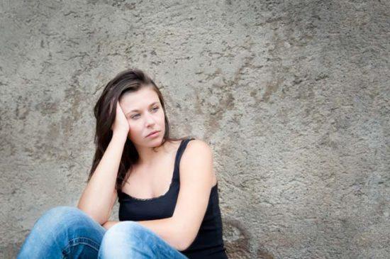 Девушка грустит у стены