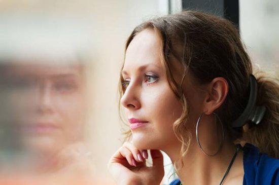 Девушка задумалась и смотрит в окно