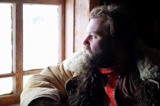 Деревенский мужчина смотрит в окно