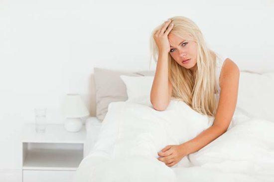 Женщина сидит на кровати