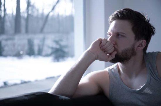 Молодой человек смотрит в окно