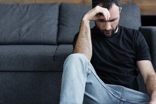 Уставший мужчина сидит у дивана
