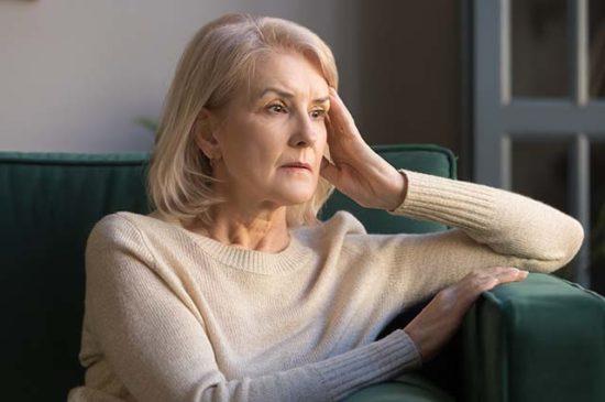 Взрослая женщина сидит и размышляет