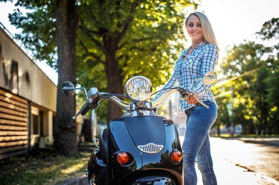 Девушка держится за руль скутера