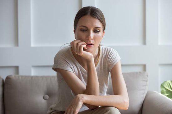 Девушка сидит и размышляет на диване