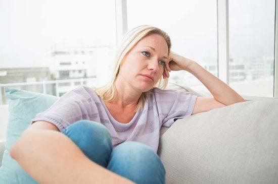 Женщина грустит на диване