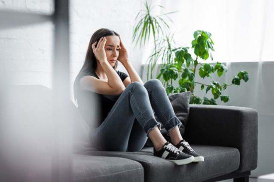 Женщина сидит на диване, расстроена