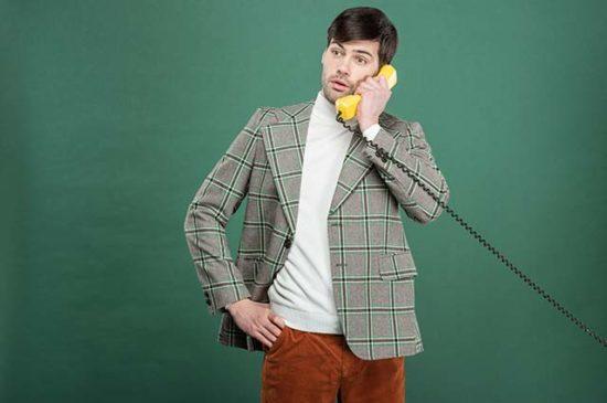 Молодой человек в винтажной одежде разговаривает по телефону