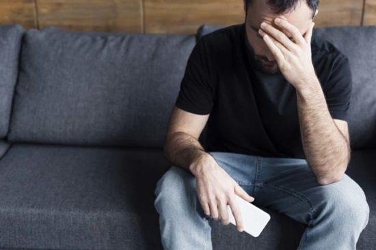 Мужчина в депрессии с телефоном на диване