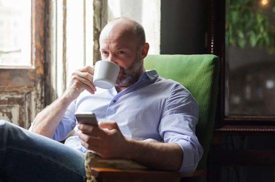 Мужчина сидит в кресле и пьёт чай