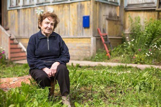 Пожилая женщина сидит во дворе
