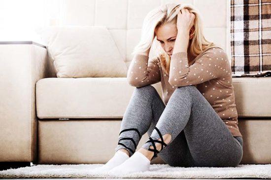Взрослая женщина сидит на полу и держится за голову