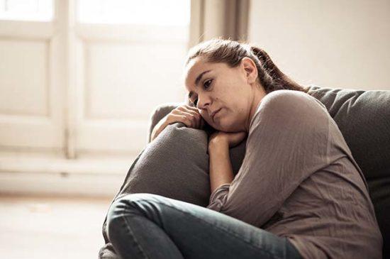 Женщина очень расстроена, лежит на диване