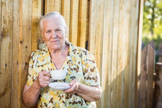 Пожилая женщина пьёт чай