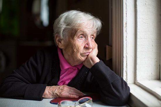 Пожилая женщина сидит у окна