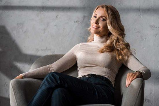 Красивая женщина средних лет сидит в кресле