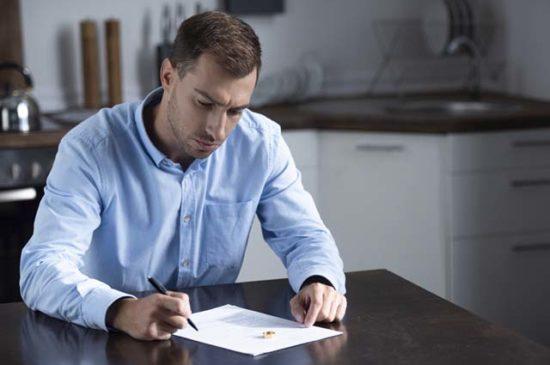 Мужчина пишет заявление о разводе