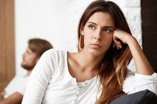 Недовольная девушка сидит на диване