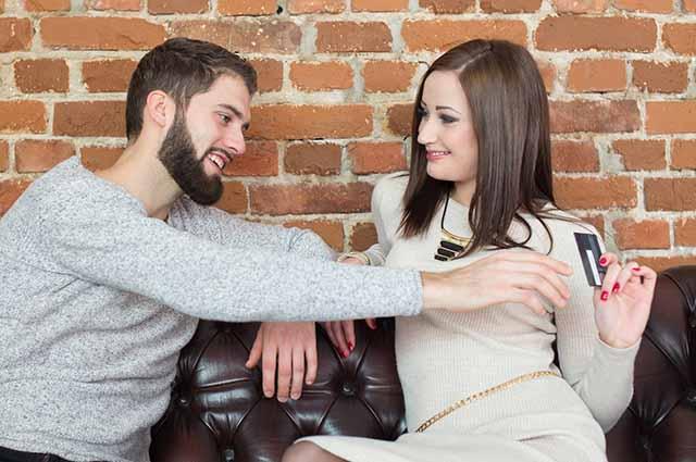 Девушка забирает кредитную карту у мужчины