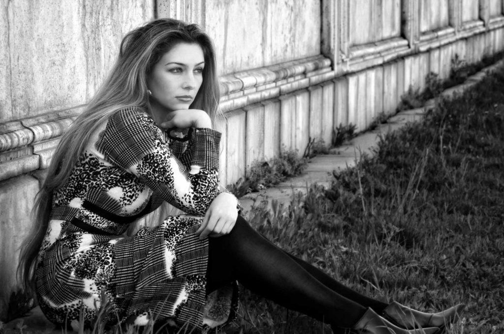 Девушка сидит на траве и грустит