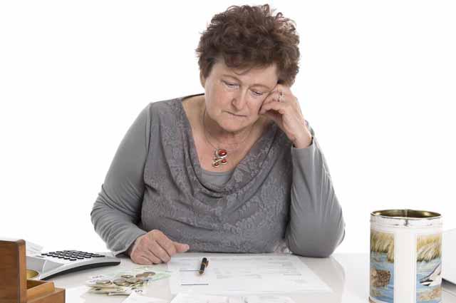 Женщина размышляет глядя на деньги