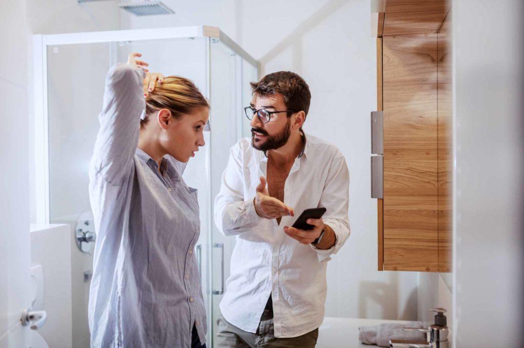 Мужчина показывает смартфон с фоткой жене