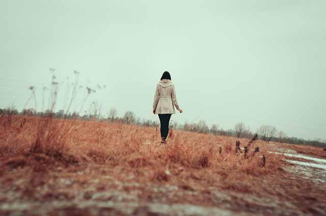 Одинокая девушка идет по полю