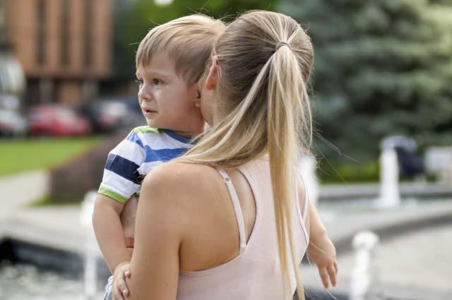 Расстроенный ребенок на руках у мамы