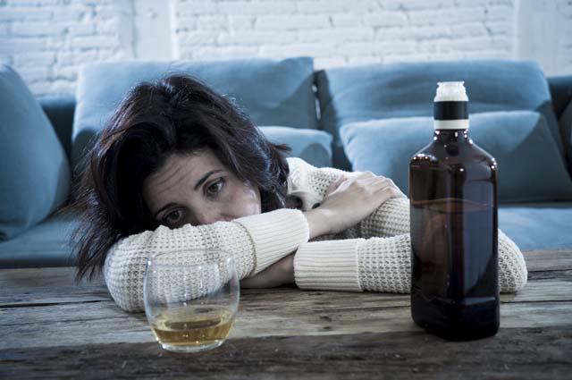 Девушка смотрит на алкоголь