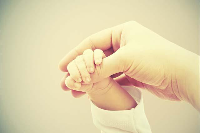 Маленькая ручка держит руку мамы