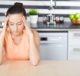 Девушка в депрессии сидит на кухне