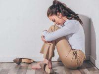Девушка после вечеринке сидит на полу