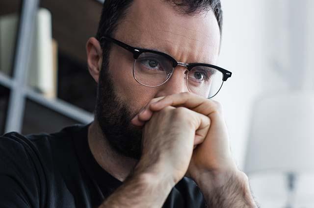 Мужчина в очках размышляет
