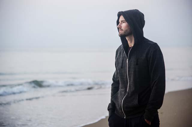 Одинокий молодой человек прогуливается по берегу