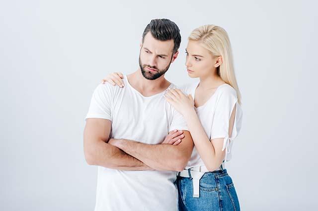 Девушка обнимает мужчину, он на неё не смотрит