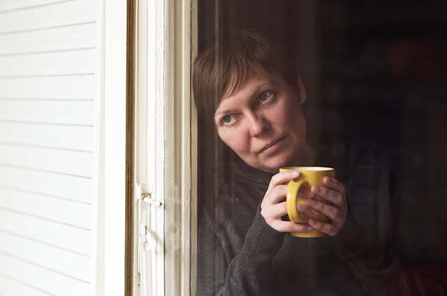 Женщина облокотилась на окно
