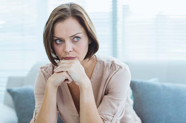 Женщина опирается на руки и размышляет
