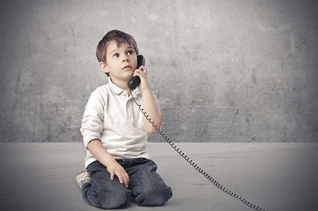 Маленький мальчик говорит по телефону