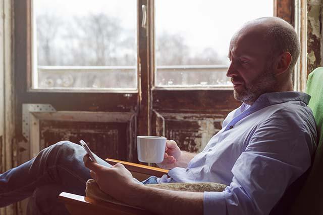 Мужчина сидит в кресле и смотрит в телефон
