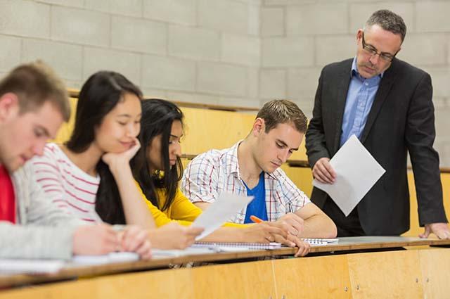 Преподаватель смотрит на работу студентов