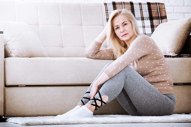 Взрослая женщина сидит на полу у дивана